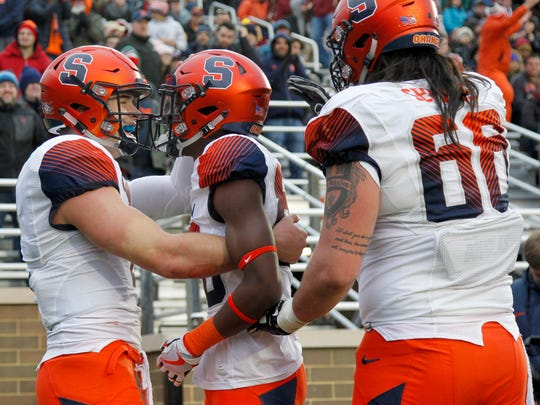 Syracuse quarterback Eric Dungey, left, celebrates with teammates Taj Harris, center, and Airon Servais (68) after Harris caught a pass for a touchdown during the second half of an NCAA college football game against Boston College, Saturday, Nov. 24, 2018, in Boston. (AP Photo/Mary Schwalm)