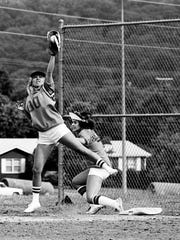 Beth Collins of ABC-Dot Lady Shindiggers is safe at first base after beating a high throw, caught by Joyce Jackson (00) of The Mary Reeves Review in the Country Music Fan Fair Softball Tournament at Two Rivers Park June 10, 1975.