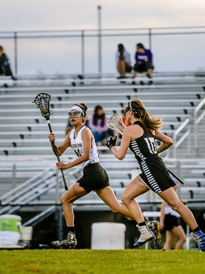 Melaina Grewal, left, of Okemos takes off toward the Haslett-Williamston goal after securing the ball on a face-off while being pursued by Bianca Kinder of Haslett-Williamston during their CAAC lacrosse championship game on May 12. Grewal is one of three juniors who surpassed 100 career points this year for the Chiefs.
