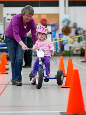 Rose Judkins, of Green Bay, helps her granddaughter Ellee Brink, 2, of Necedah, complete the bike rodeo during the Children's Festival at Marshfield High School on Saturday.