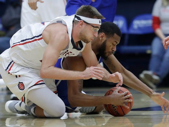 UNC-Asheville guard Ahmad Thomas and Saint Mary's (Cal.) forward Calvin Hermanson, reach for the ball during the first half of an NCAA college basketball game in Moraga, Calif., on Friday December 22, 2017.
