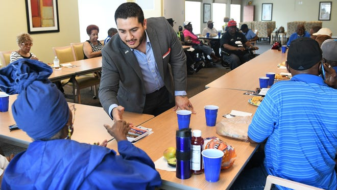 Democratic gubernatorial candidate Abdul Al-Sayed shakes hands with resident Regina Lawson at the Thome Rivertown Senior Apartments in Detroit on July 12, 2018.