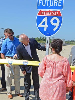 Arkansas Gov. Asa Hutchinson, center, checks out a highway sign prior to a ribbon cutting during the Highway 549/Future I-49 dedication in July 2015.