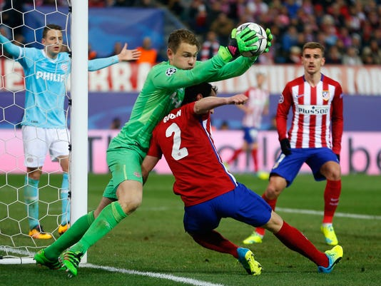 Atletico's Diego Godin collides with PSV goalkeeper Jeroen Zoet during the Champions League second leg soccer match between Atletico Madrid and PSV Eindhoven at the Vicente Calderon stadium in Madrid, Spain, Tuesday March 15, 2016. (AP Photo/Francisco Seco)