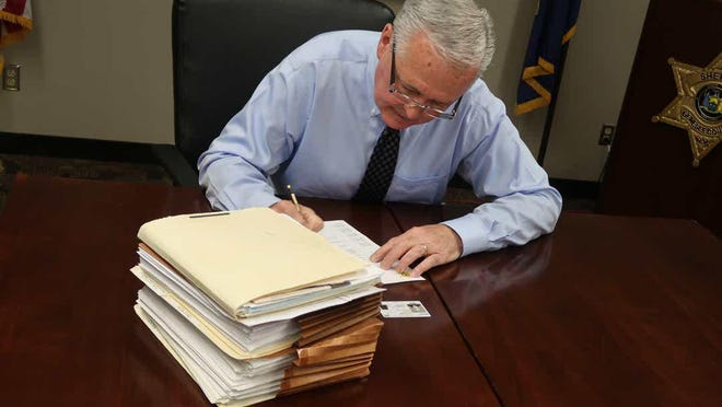 Sheriff William Sheron Jr. signs a form authorizing the release of his police personnel file to a reporter from the Democrat and Chronicle on July 15.