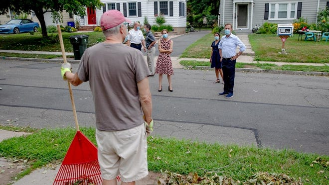 Gov. Ned Lamont talks to Dave Lynch who was cleaning his neighborhood on Thursday in West Hartford. Lynch said his house has been out of power and internet.