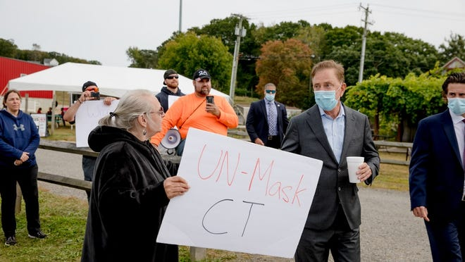 Gov. Ned Lamont talks to Melanie MacDonald, left, of New Britain, who protests against his executive orders related to the coronavirus pandemic. One of the protestors, Aaron McCool, in the orange shirt, argued against the order to wear a mask.