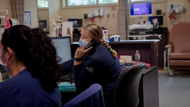 Kristin Levine, right, a registered nurse, calls a patient on the phone on Thursday, Oct. 1 at Bristol Hospital. Connecticut is one of the few states that don't have a singular place where every medical practitioner involved with a patient can access that person's health information. Connecticut has been working on that system for over a decade and plans to finally launch one this fall.