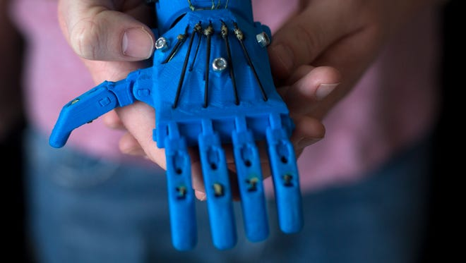 Tue., Feb. 14, 2017: Derryn Scott, a fifth-year biomedical engineering student at the University of Cincinnati, holds a 3D-printed prosthetic that Enable UC, a student organization, produced.