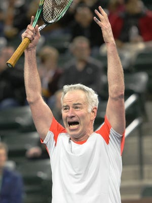 """Tennis legend John McEnroe """"celebrates"""" a shot during the McEnroe's Challenge for Charity tennis event at the Indian Wells Tennis Garden on March 1, 2014."""