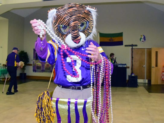 The LSU tiger delights the crowd throwing beads during