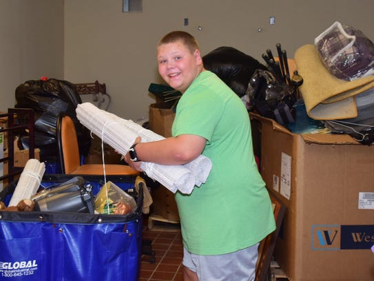 Aiden Spencer helps unpack one of the many bins filled