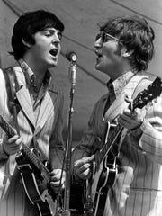 Paul McCartney (left) and John Lennon of the Beatles perform at Crosley Field.