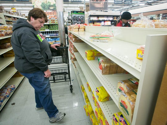 Laureen Valentine of Pike Creek looks at the bread section which is going fast as shoppers crowd into Zingo's Supermarket grabbing bread and other items in preparations for the coming weekend snow storm.