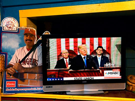 A cardboard advertisement displaying a Hispanic baseball player sits beside a television broadcasting President Donald Trump's first State of the Union address Tuesday. The TV was at El Fenix Cafe in Abilene where local Democrats had gathered to watch the speech, but left before it ended.