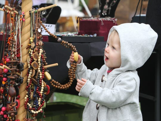 A youngster looks at a necklace at the Ozark Arts and