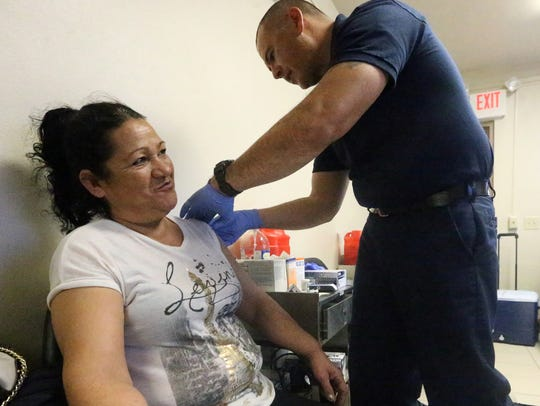 Yolanda Palomares of El Paso gets a flu vaccination from El Paso Fire Department paramedic Lt. Edward Montoya.