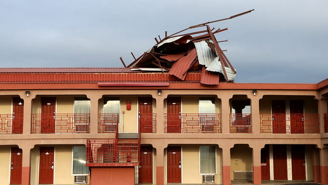 The part of the roof at the Knights Inn hotel is left crumpled after a severe storm hit San Angelo Friday, June 23, 2017.