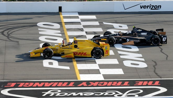 Ryan Hunter-Reay (28) waves his hand as he takes the checkered flag under caution ahead of Josef Newgarden (67) to win the Pocono IndyCar 500 auto race Sunday, Aug. 23, 2015, in Long Pond, Pa. Newgarden finished second. (AP Photo/Mel Evans)