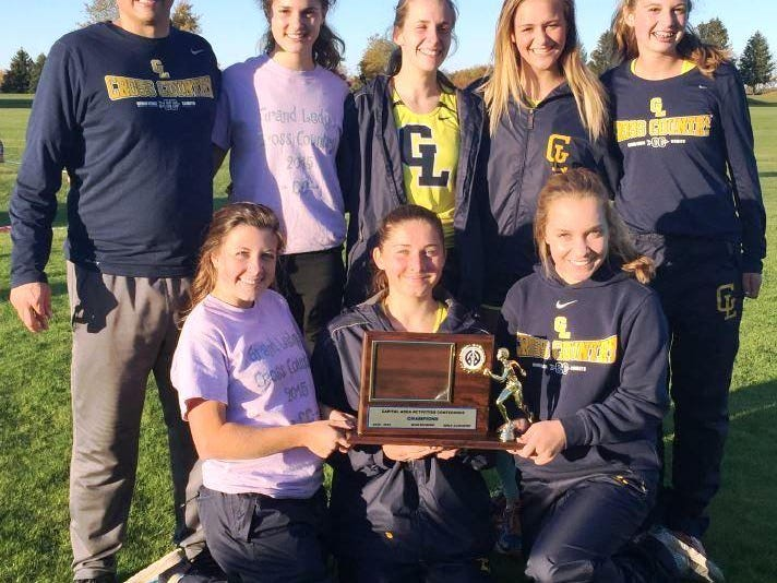 Coach Fred Hutchinson and Grand Ledge girls cross country team celebrate after winning the title at Grand Ledge Meadows Country Club Oct. 22. The team took part in the state regional meet last Friday. Standing (l to r) Hutchinson, Jenna Magness, Claudia Baryo, Morgan Arnouts, Michaela Donahue. Bottom (l to r) Annmarie Maher, Becky Golisch and Grace Johnson.