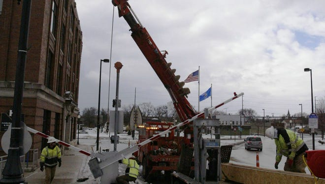 Crews work to repair a control box for the 8th Street Bridge Thursday, Jan. 28. The box was damaged in a hit-and-run accident last October.