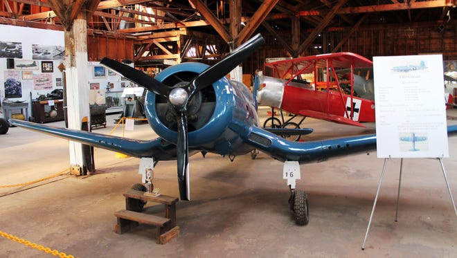 Multiple aircraft, ground vehicles and engines are on display in the showroom of the Kingman Army Air Field Museum.