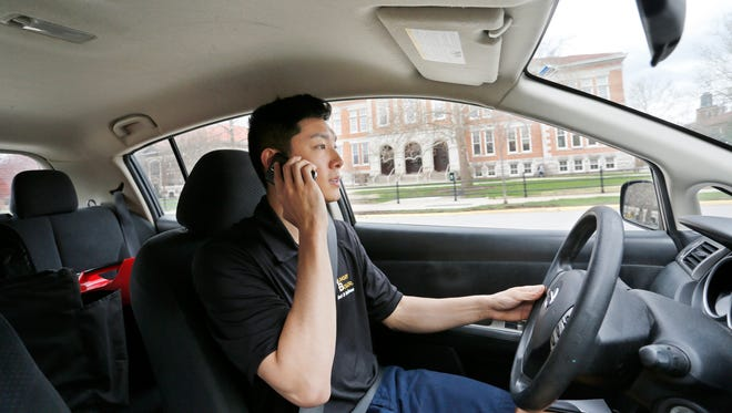 HungryBoiler driver Eric Koo calls his customer as he makes a delivery Monday, March 28, 2016, in West Lafayette. On this run, Koo delivered two bubble tea drinks from Latea Bubble Tea Lounge to a Purdue University student in First Street Towers.