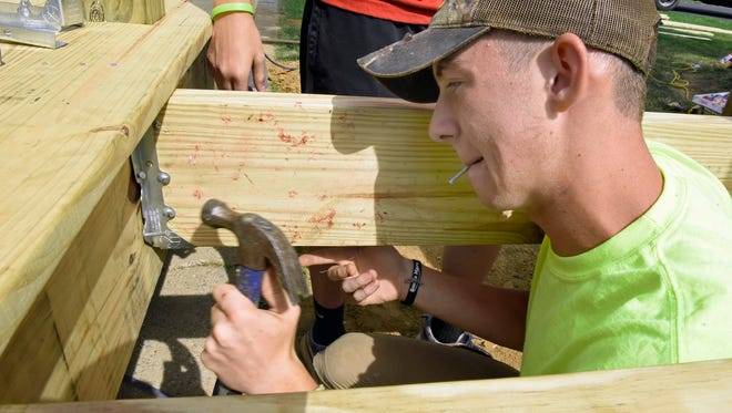 Luke Ritz, 17, works to build a new porch and ramp at a Shippensburg mobile home on Tuesday, July 12, 2106.