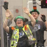 Members of the Howell robotics SCOTS BOTS Team 4776 sway to music thundering over speakers during a pause in the competition at Mason High School. From left are coach Chuck Nester, Liz Talbot and Max Chriensen. Not seen is team member Domenic Portuesi.