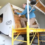 Jim Koronich removes water-damaged materials on a trailer at Camper/Trailer Parts & Repair near Fowlerville. Koronich, 51, is employed at the shop through its partnership with Genesis House in Fowlerville.