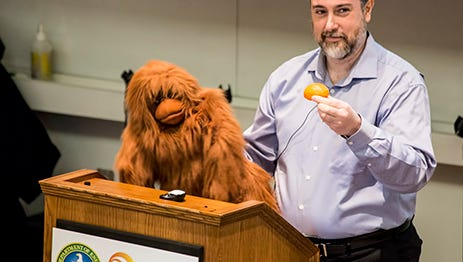 "Michael Graziano, a neuroscientist and professor at Princeton University, discusses ""Consciousness and the Social Brian,"" with the help of an orangutan puppet named ""Kevin"" in a Science on Saturday lecture in January of 2015."