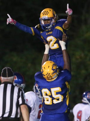 A.I. du Pont's Naz'Aire Miller is hoisted in the air after a touchdown by teammate Eddy Peguero in the second quarter at A. I. du Pont High School.