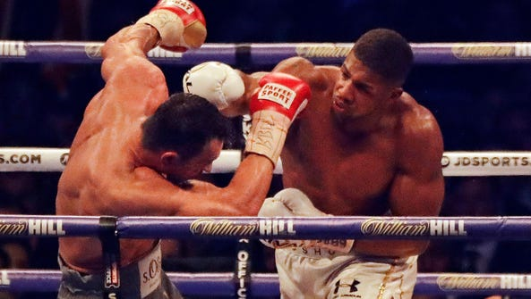 Anthony Joshua, right, delivers a blow to Wladimir