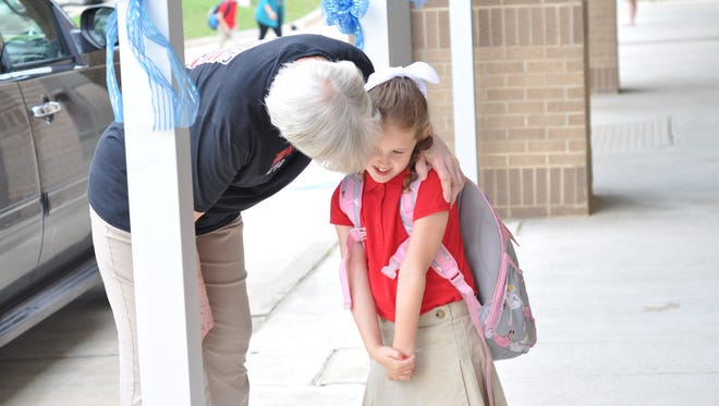 Pre-K teacher Cathy Blakemore greets J.I. Barron Sr. Elementary School students, including Willow Stroud, with a hug on the first day of school.