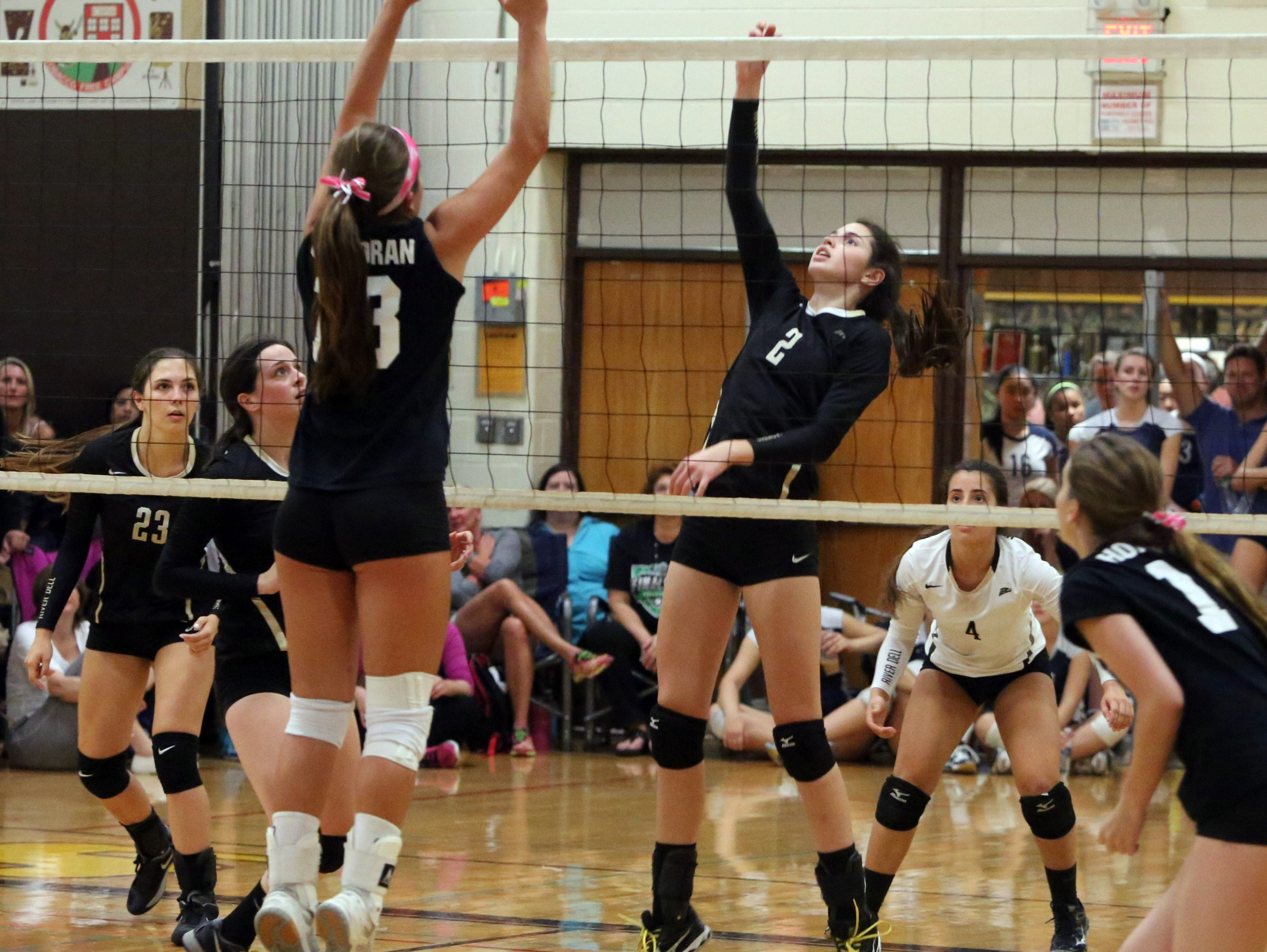 River Dell's Christine Woods puts up a shot over Demarest's Victoria Corcoran as the Clarkstown South High School held their volleyball tournament for area teams at the school, Sept. 26, 2015.