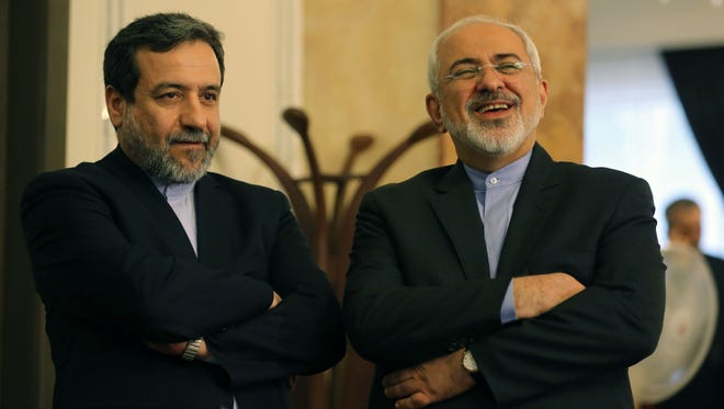 Iranian Foreign Minister Javad Zarif, right, and Deputy Foreign Minister and chief nuclear negotiator Abbas Araghchi react as they listen to President Hassan Rouhani (unseen) speaking during a press conference in Tehran on April 3, 2015.