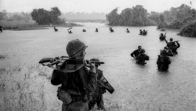 Paratroopers of the U.S. 2nd Battalion, 173rd Airborne Brigade hold their automatic weapons above water as they cross a river in the rain during a search for Viet Cong positions in the jungle area of Ben Cat, South Vietnam, Sept. 25, 1965.