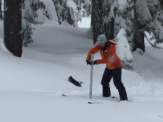 Julie Koeberle, a hydrologist with NRCS measures snow