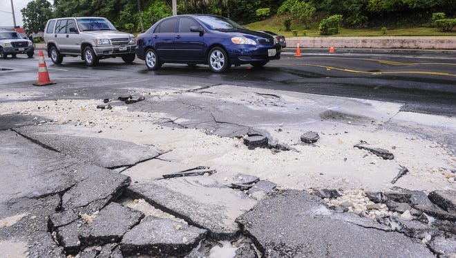Motorists drive through a portion of Marine Corps Drive riddled with broken or rolling sections of asphalt on Monday, July 20. Traffic was backed up in both the northbound and southbound lanes after after police restricted travel through the area to one lane in each direction.