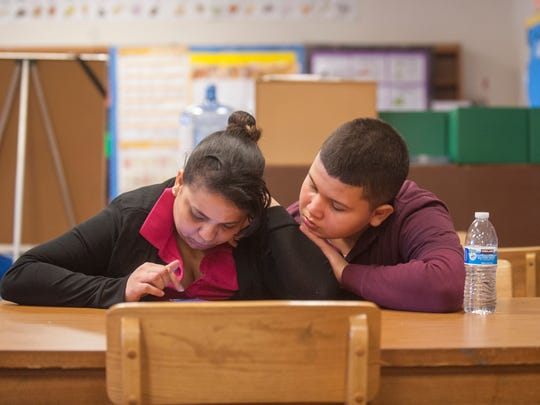 Jashuel Ramirez sits with his mother Katira Ramos in the library of the Veteran's Memorial School in Camden. Ramirez and Ramos were displaced to Camden from Puerto Rico after they lost their family farm in Hurricane Maria.  Ramirez currently attends the Veteran's Memorial School in Camden. 12.13.17