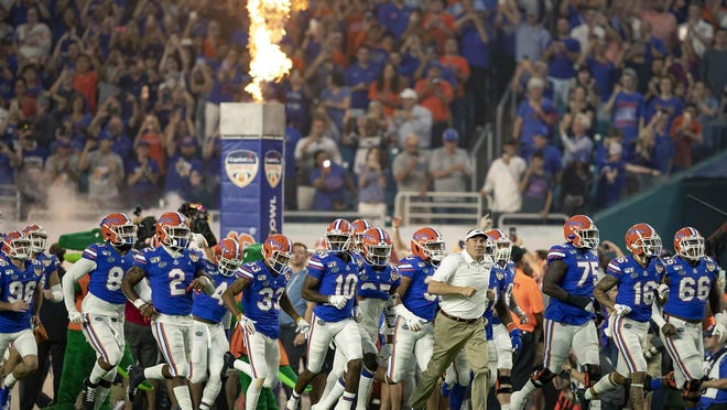 Florida Gators head coach Dan Mullen leads his team onto the field at the Orange Bowl at Hard Rock Stadium in Miami Gardens.