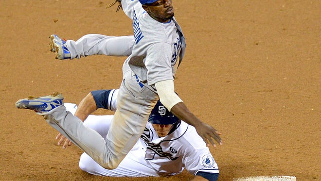 JLos Angeles Dodgers second baseman Dee Gordon (9) throws to first as San Diego Padres first baseman Tommy Medica (bottom) slides to break-up the double-play during the sixth inning at Petco Park.