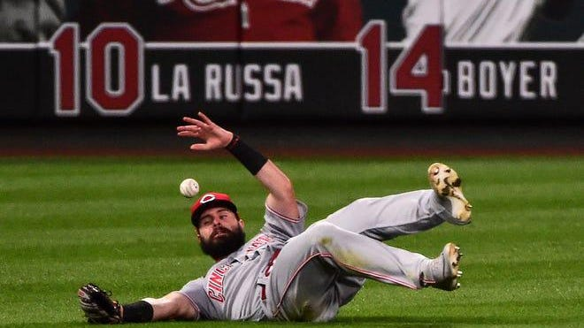 Cincinnati Reds left fielder Jesse Winker dives but is unable to catch a single hit by St. Louis Cardinals second baseman Kolten Wong during the third inning of a Major League Baseball game at Busch Stadium in St. Louis on Aug. 22, 2020.