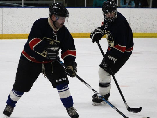 The Rev. Paul Graney (left) skates the puck up the ice during Friday's game against Sacred Heart Major Seminary.