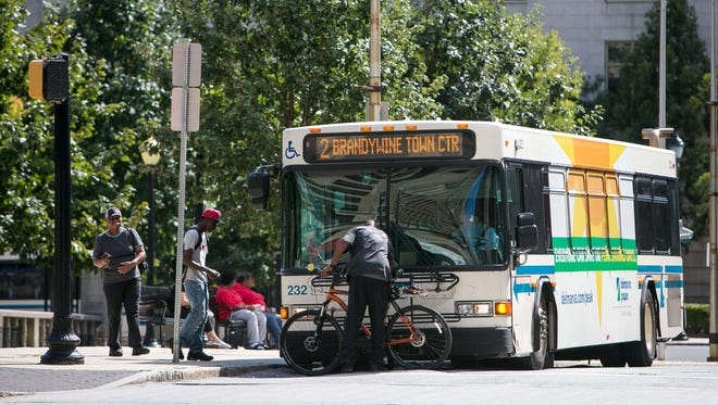 Riders wait for the bus in Rodney Square in Wilmington.