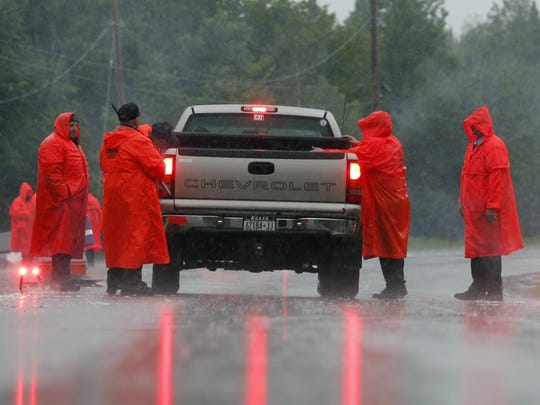 Corrections officers check a vehicle at a roadblock on Sunday in Malone, N.Y.