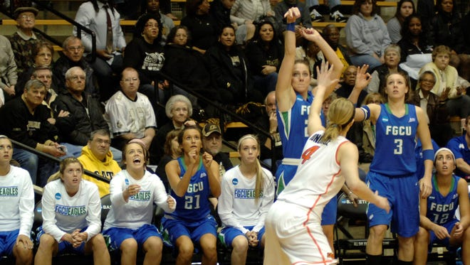 The FGCU Eagle bench reacts as Jenna Cobb launches a three-point shot.