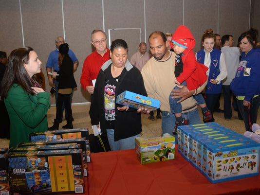 ANI Rotary TT Doll and Toy FundJordan Buchanan (far left, green coat) and Jay Lynch (back, red shirt), both with the Rotary Club of Alexandria, help Sharon Roberts (second from left, black coat) and Harvey McNeal (beige shirt) shop look for a gift for son Ladarius Roberts, 2, at the annual Doll & Toy Distribution sponsored by the Rotary Club of Alexandria and The Town Talk. The event was held Saturday, Dec. 20, 2014 at Alexandria Convention Hall in downtown Alexandria.-Melinda Martinez/mmartinez@thetowntalk.com The Town Talk, Gannett