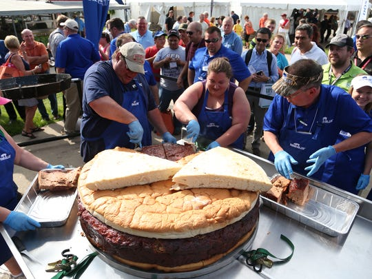 Gary Vinsand of Dakota City, Iowa, carves up carves up the world's largest pork burger, created at the World Pork Expo in 2014.
