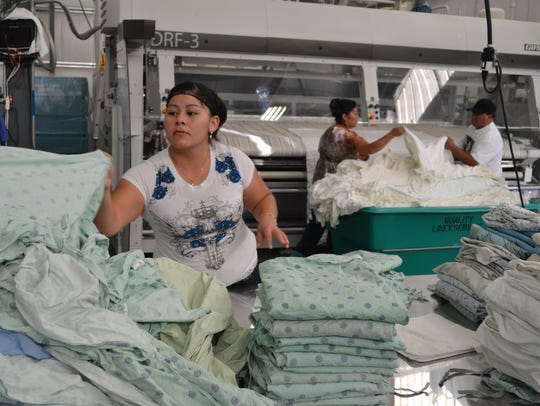A worker folds hospital gowns at Quality Linen Service